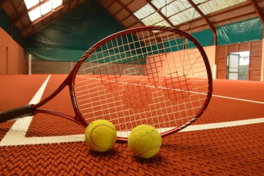 Court de tennis vu a travers une raquette de tennis. Deux balles posees devant